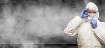 Человек нося костюм и изумленные взгляды Hazmat в знамени комнаты Smokey с космосом экземпляра стоковая фотография rf