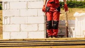 Человек нося красные брюки работника стоковая фотография