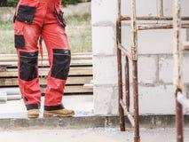 Человек нося красные брюки работника стоковые фотографии rf