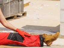 Человек нося красные брюки работника стоковое изображение