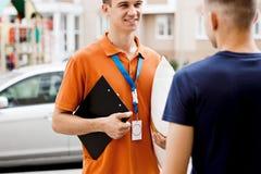 Человек нося оранжевую футболку и бирку имени и держа доску сзажимом для бумаги поставляет пакет к клиенту содружественно стоковые изображения