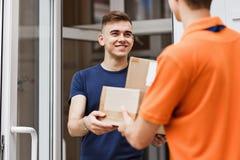Человек нося оранжевую футболку поставляет пакеты к удовлетворенному клиенту Дружелюбный работник, высококачественная доставка стоковая фотография