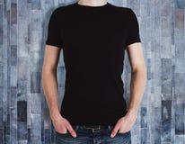 Человек нося пустую рубашку на деревянной предпосылке стоковые фото