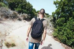 Человек нося рюкзак идя грязной улицей стоковые изображения