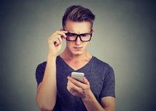 Человек нося стекла имея тревогу видя сотовый телефон имеет проблемы зрения стоковое фото rf