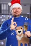 Человек нося теплое голубое владение свитера оленей в шампанском руки Стоковые Изображения RF