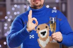 Человек нося теплое голубое владение свитера оленей в шампанском руки Стоковое Изображение RF