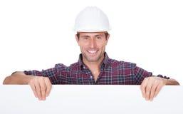 Человек нося трудный шлем проводя плакат Стоковое фото RF