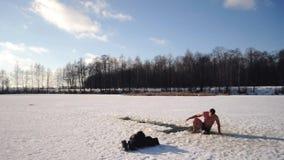 Человек ныряет в отверстие на морозный день, ясный зимний день на заморозках явления божества, русская традиция для того чтобы по сток-видео