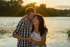 Человек обнимает молодую женщину на предпосылке захода солнца Стоковая Фотография RF