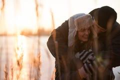 Человек обнимая его женщину плотно от позади стоковое фото