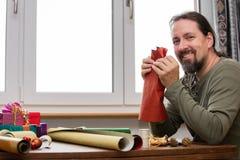 Человек оборачивает красочные подарки стоковое фото