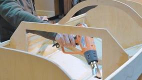 Человек обрабатывает швы шлюпки, он нагревает с феном для волос Это сделано для закрепленности Делающ корабль вручную видеоматериал