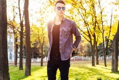 Человек одетый в стильных одеждах, солнечных очках, прогулках в парке, стоковое фото