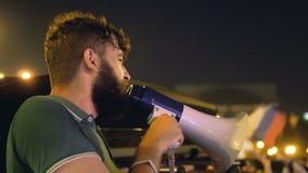 Человек около автомобиля и громкоговорителя агитирует на забастовке Сердитые люди дают сильную речь сток-видео