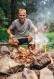 Человек около лагерного костера подготавливает vegetabels для гриля Стоковое Изображение RF