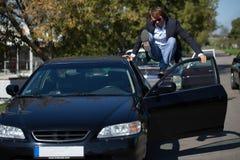 Человек около черного автомобиля в скакать костюма стоковая фотография rf