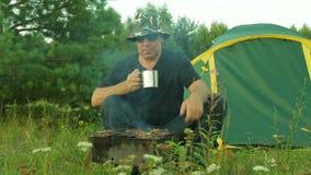 Человек около шатра, выпивая чая и поворачивать мясо на гриле видеоматериал