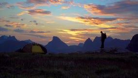Человек около шатра смотрит рассвет сток-видео