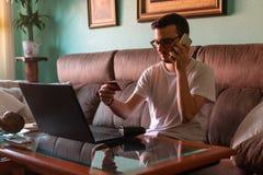 Человек оплачивая с кредитной карточкой на ноутбуке дома стоковое фото rf