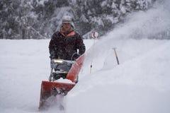 Человек освобождает подъездную дорогу во время шторма зимы стоковые фото