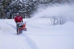 Человек освобождает подъездную дорогу во время шторма зимы стоковая фотография