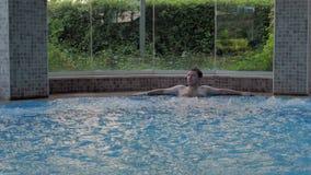 Человек ослабляет в бассейне джакузи на спа-курорте, наслаждаясь роскошной жизнью Здоровый образ жизни, успех _ сток-видео