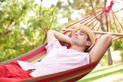Человек ослабляя в гамаке Стоковая Фотография RF