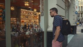 Человек осматривает витрину магазина сувенира в старом touristic городе в летнем дне сток-видео