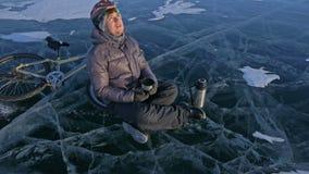Человек отдыхает сидеть на колесе велосипеда на льде Он выпивает чай от бутылки thermos Велосипедист одет видеоматериал