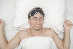 Человек отдыхая в маске для сна Стерня на его стороне утомлянный человек стоковое изображение