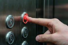 Человек отжимает кнопку лифта стоковое изображение