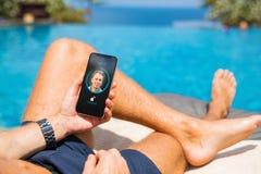 Человек открывает мобильный телефон с лицевой технологией опознавания Стоковая Фотография RF