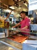 Человек отрезает, аранжирует сосиску Вены на Zum goldenen стойка сосиски Wuerstel в Вене, Австрии стоковое фото