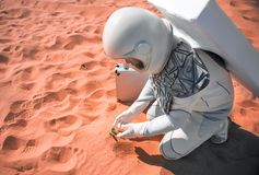 Человек от космоса размещая около малой травы Стоковые Фото