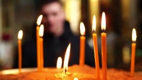 Человек от afar смотрит свечи горя в подсвечнике в христианской церков сток-видео