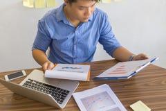 Человек офиса проверяя финансовый номер на отчете стоковое изображение