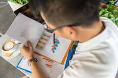 Человек офиса читая финансовый номер на документе стоковые изображения