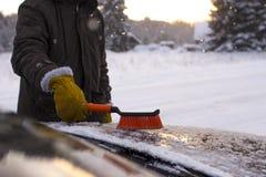 Человек, очищает автомобиль от снега Стоковая Фотография