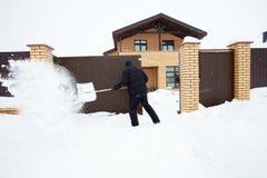 Человек очищает лопаткоулавливатель снега Стоковые Изображения