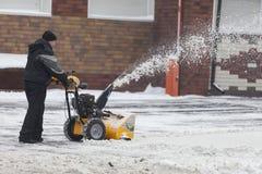 Человек очищает снег от тротуаров с snowblower стоковые изображения rf