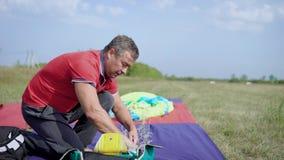 Человек пакует парашют, прикрепляя ремни в outdoors рюкзака в летнем дне в зеленых полях акции видеоматериалы