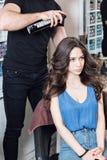 Человек парикмахера крупного плана делает стиль причёсок для молодой женщины в салоне красоты Стоковое фото RF