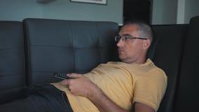 Человек переключает дистанционное управление ТВ наблюдать tv акции видеоматериалы