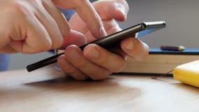 Человек печатает в smartphone и занимается серфингом в интернете сток-видео