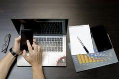 Человек печатает на компьтер-книжке, лежа рядом с телефоном, glasse таблетки стоковые фотографии rf