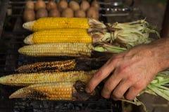 Человек печет мозоль и картошки на гриле стоковая фотография rf