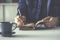 Человек писать его тетрадь на таблице Стоковые Фото
