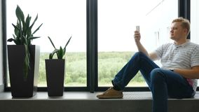 Человек пишет SMS и смотрит вне окно авиапорта Парень говорит в посыльных Молодой человек в smartphone играет видеоматериал
