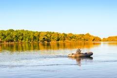 Человек плавает резиновой шлюпкой вниз с реки на восходе солнца Стоковая Фотография